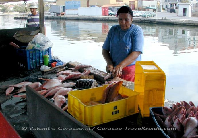 Fish market - Woman cleans the fish